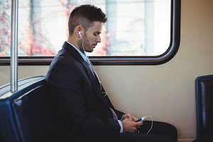 Businessman listening to music and using on mobile phone