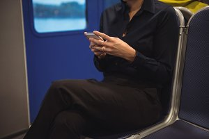 Businesswoman using phone while sitting