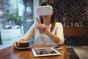 Businesswoman using vr headset while sitting at table with coffee, digital tablet and phone