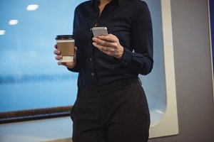 Businesswoman with coffee cup using phone while standing in train