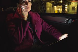 Businesswoman with digital tablet talking on phone