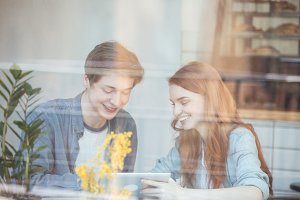 Young couple using smartphone behind glass