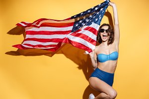 Happy young lady in swimwear holding USA flag.