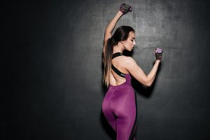 Back view of a healthy woman in sportswear holding dumbbells