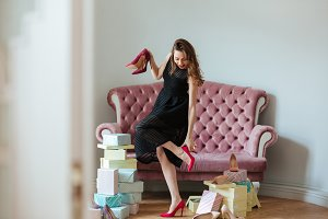 Happy young lady standing near sofa indoors choosing shoes