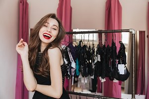 Happy woman standing in clothes shop indoors choosing lingerie