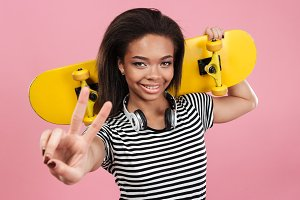 Portrait of a smiling afro american teenager girl holding skateboard