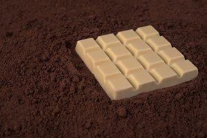 White chocolate bar over milk chocolate powder