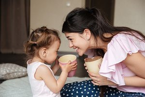 Happy young mother drinking tea with her little daughter
