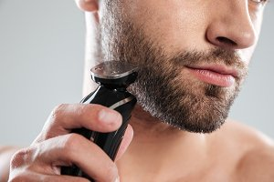 Cropped image of a young bearded man using electric shaver