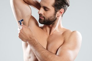 Portrait of a young bearded man shaving his armpit