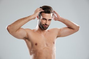 Charming naked bearded man posing and touching his hair