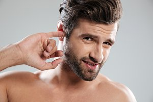 Young impolite guy picking his ear and looking at camera