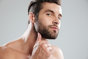 Portrait of a handsome naked bearded man examining his face