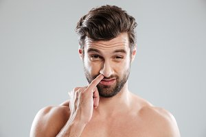 Portrait of a young bearded naked man picking his nose