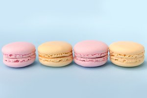 Four sweet colorful macaroons on blue table background.