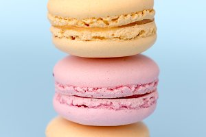 Three sweet colorful macaroons on blue table background.
