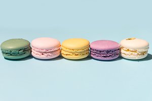 Five sweet colorful macaroons on blue table background.