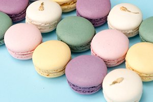 Sweet colorful macaroons on blue table background.