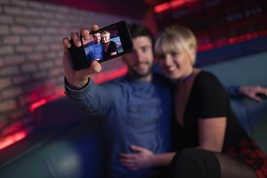 Couple taking selfie on mobile phone in bar