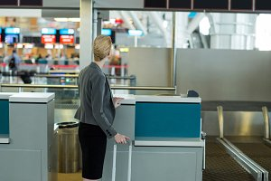 Rear view of businesswoman standing at a check-in counter with luggage