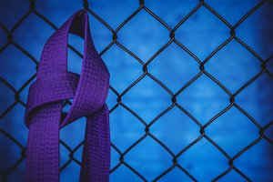 Karate purple belt hanging on wire mesh fence