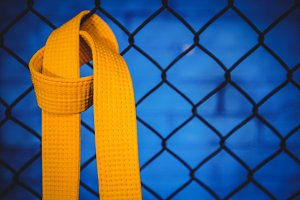 Karate yellow belt hanging on wire mesh fence