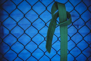 Karate green belt hanging on wire mesh fence