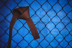 Karate brown belt hanging on wire mesh fence