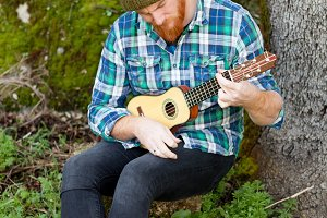 Red haired guy playing a guitar