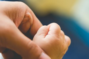 Mom hold her small baby hand