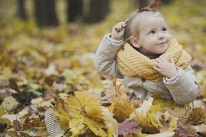 Little happy baby girl plays in autumn park among yellow leaves