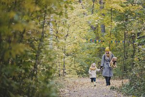 Mother and her daughter little girl walking in a autumn park