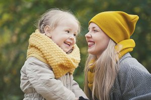 Little blonde girl with her mommy in autumn park - play and clap hands, close up