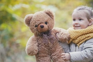 Little blonde girl plays with teddy bear in autumn park