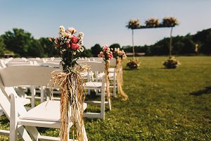 Pink bouquets beautify white chairs