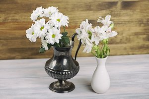 Flowers in an iron vase and in a ceramic vase. Daisies and lilies.