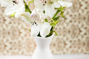 Flowers in white ceramic vase on decorated paper background. Lilies. Vertical shoot.