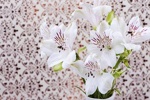 Flowers in white ceramic vase on decorated paper background. Lilies.