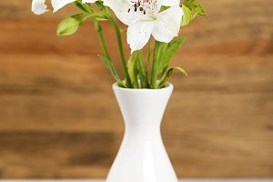 Flowers in a ceramic vase. Daisies and lilies. Vertical shoot.