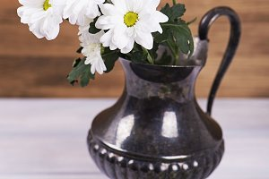 Close-up of flowers in iron vase on wooden table. Daisies and lilies. Vertical shoot.