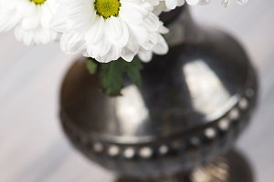 Close-up of flowers in iron vase on wooden table.Vertical flower.