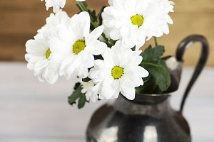 Close-up of flowers in iron vase on wooden table. Daisy flower.