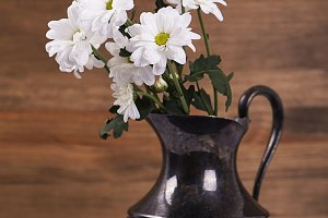 Flowers in iron vase on wooden table. Daisy flower. Vertical shoot.