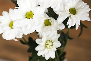 Close-up of flowers in a glass vase with water on wooden background. Daisy flower. Vertical shoot.