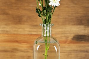 Flowers in a vase with water on wooden table. Decor. Vertical shoot.