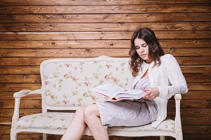 girl in white clothes on a bench with a book