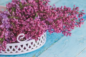 Bouquet of violet lilac in the decorative violet tray