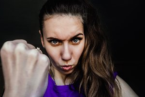 Portrait of an angry girl. Shows a fist