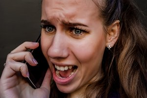The girl is shouting on the phone. Conversation in anger